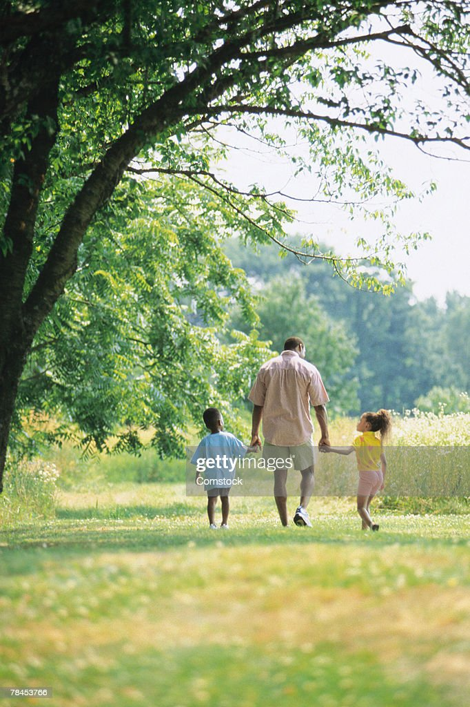 Father and children walking in park and holding hands : Stockfoto
