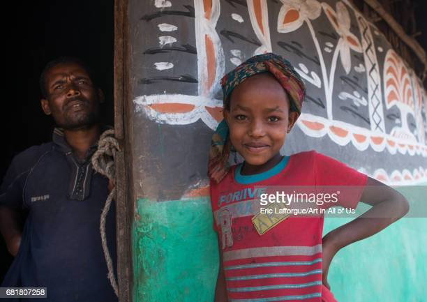 Father and daiughter standing in front of a traditional painted house Kembata Alaba Kuito Ethiopia on March 9 2016 in Alaba Kuito Ethiopia