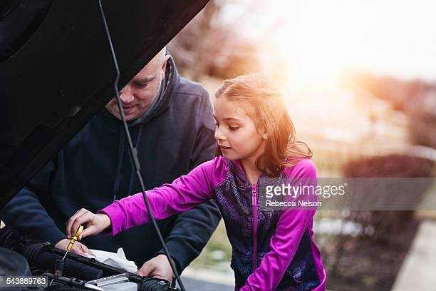 father and daugher checking oil in car