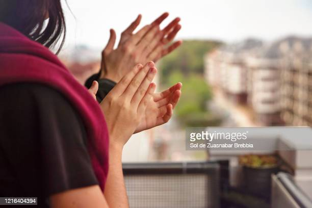 father and daughter applauding from the balcony of their home - applauding stock pictures, royalty-free photos & images