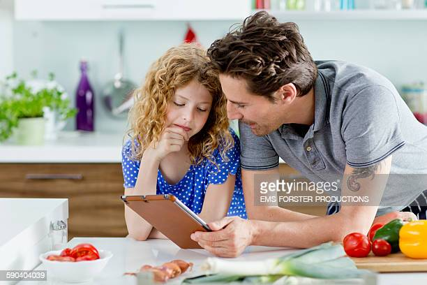 father and daughter are looking on tablet pc