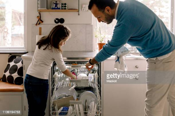 father and daughter arranging utensils in dishwasher at kitchen - family with one child stock pictures, royalty-free photos & images