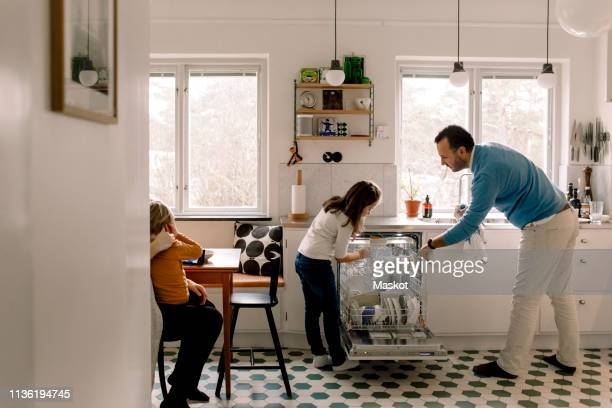 father and daughter arranging utensils in dishwasher while standing at kitchen - couples showering stock pictures, royalty-free photos & images