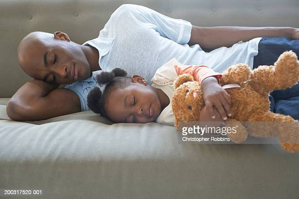 Father and daughter (2-4) asleep on sofa