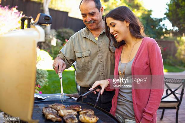 Father and daughter at barbecue grill in garden