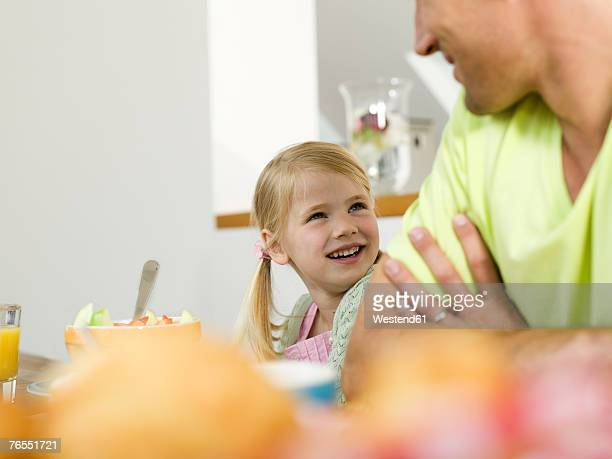 Father and daughter (6-7) at breakfast table, smiling
