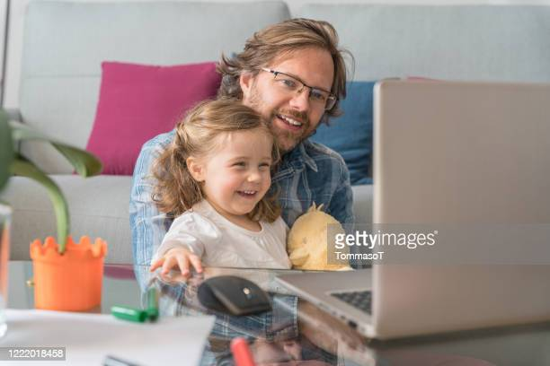 vader en dochter thuis die pret hebben die op een laptopscherm letten - onschuld stockfoto's en -beelden