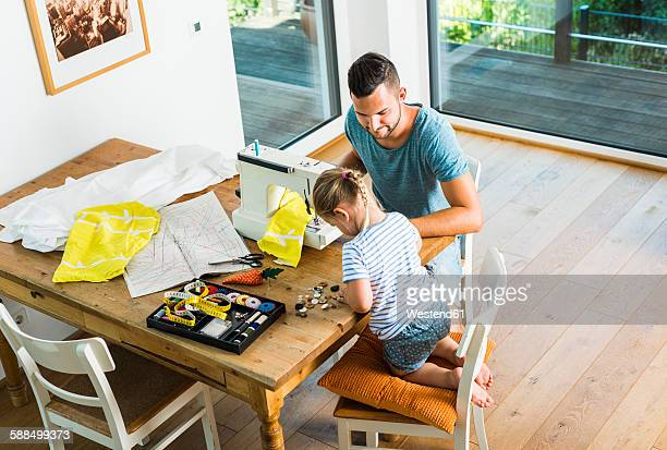 father and daughter at home using sewing machine - family with one child stock pictures, royalty-free photos & images