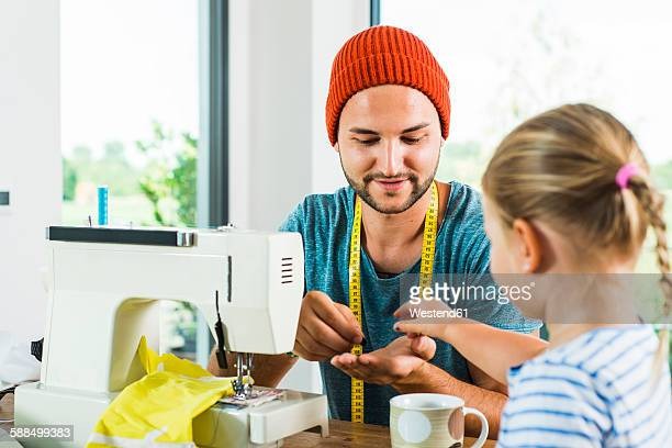 father and daughter at home using sewing machine - role reversal stock photos and pictures
