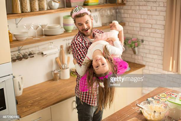 Father and daughter baking and playing in kitchen.