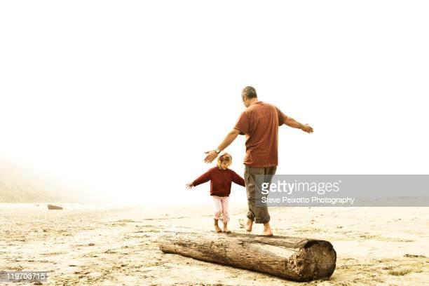 Father and daughter balancing on log