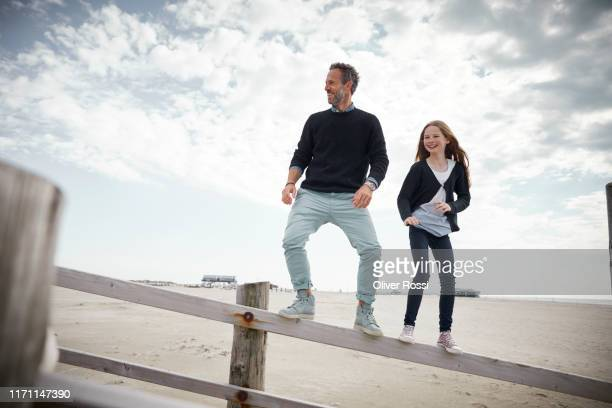 father and daughter balancing on railing of boardwalk on the beach - schleswig holstein stock pictures, royalty-free photos & images