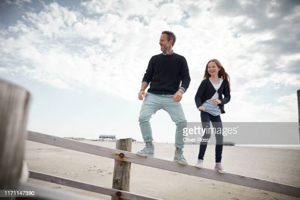 father and daughter balancing on railing of boardwalk on the beach - schleswig holstein stock-fotos und bilder