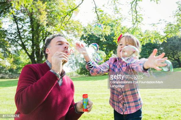 father and daughter blowing bubbles in garden - maroon stock pictures, royalty-free photos & images
