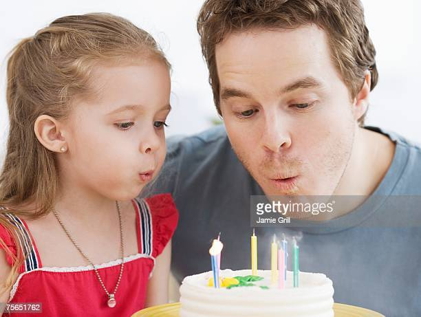 Father and daughter blowing out birthday candles