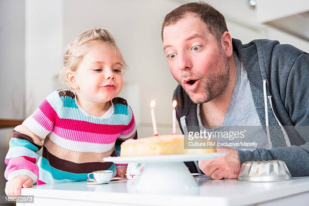 Father and daughter blowing out candles on birthday cake