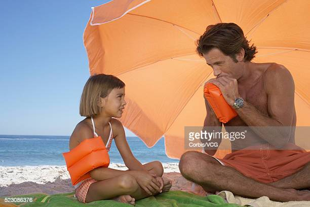 Father and Daughter Blowing up Water Wings