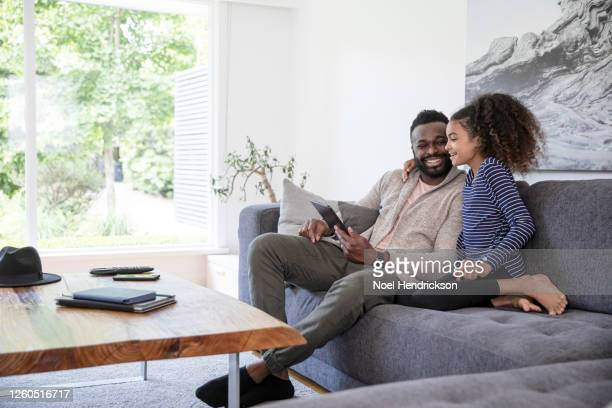 father and daughter bonding with tablet device - mid adult stock pictures, royalty-free photos & images