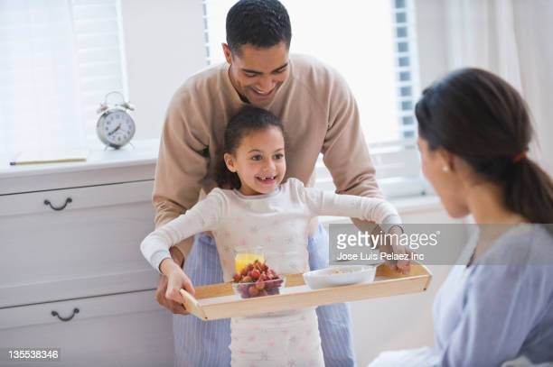 father and daughter bringing breakfast to mother - breakfast in bed stock pictures, royalty-free photos & images