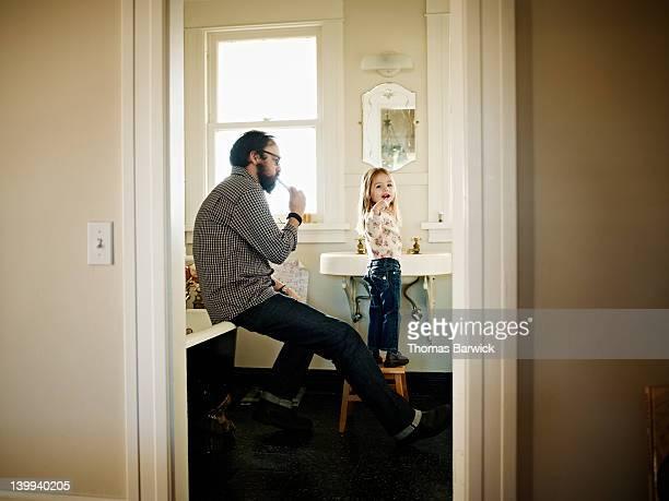 father and daughter brushing teeth in bathroom - badkamer huis stockfoto's en -beelden