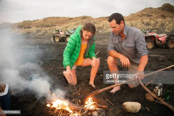 father and daughter building fire at beach - simple living stock pictures, royalty-free photos & images