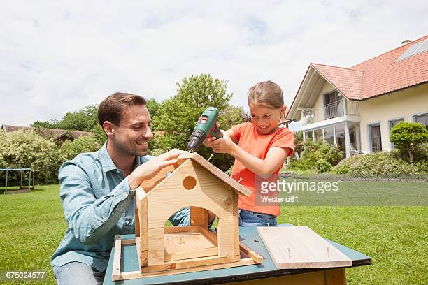 Father and daughter building up a birdhouse