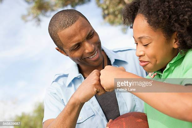 Father and daughter (13-15) bumping fists