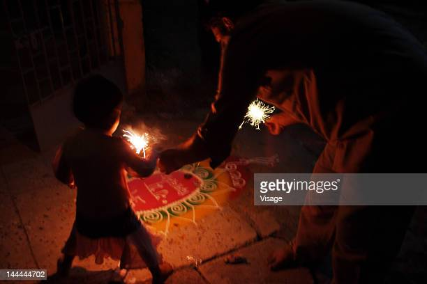 Father and daughter burning crackers on Diwali