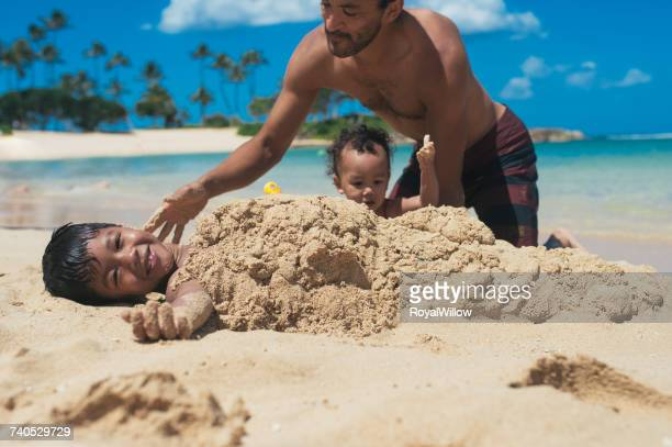 father and daughter burying son in sand on the beach - burying stock pictures, royalty-free photos & images