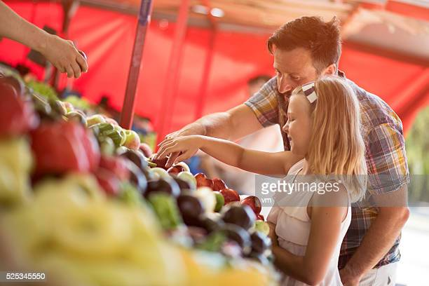 Father and daughter buying on farmers market