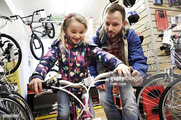 father and daughter choosing bike in shop