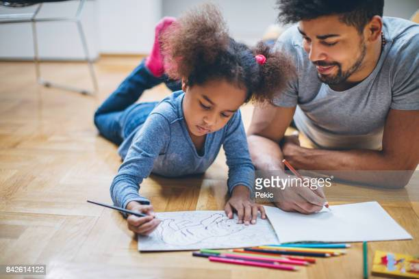 father and daughter coloring together - colouring stock photos and pictures