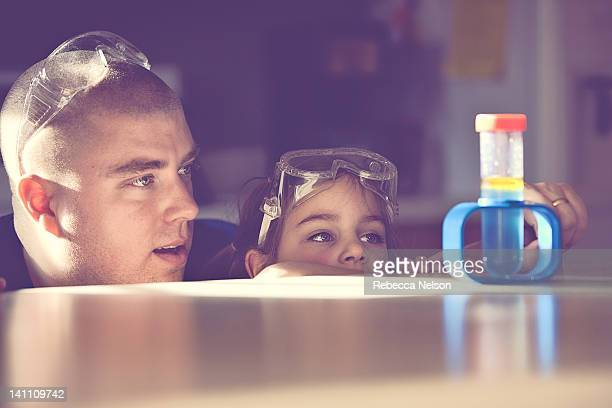 father and daughter conducting science experiment - leanintogether stock pictures, royalty-free photos & images