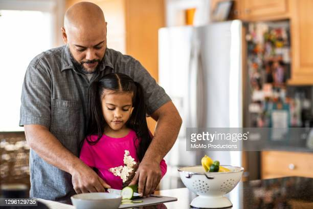 father and daughter cooking in kitchen - genderblend stock pictures, royalty-free photos & images