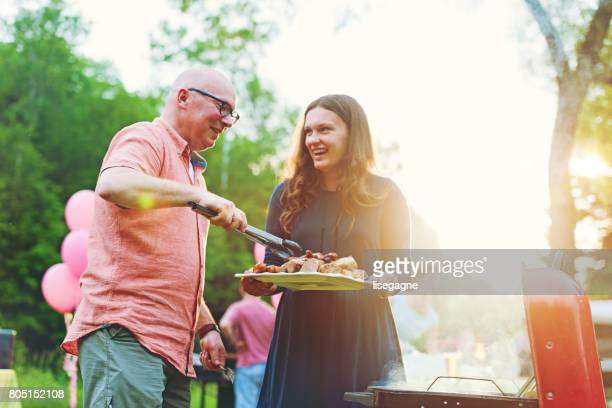 Father and daughter cooking on barbecue