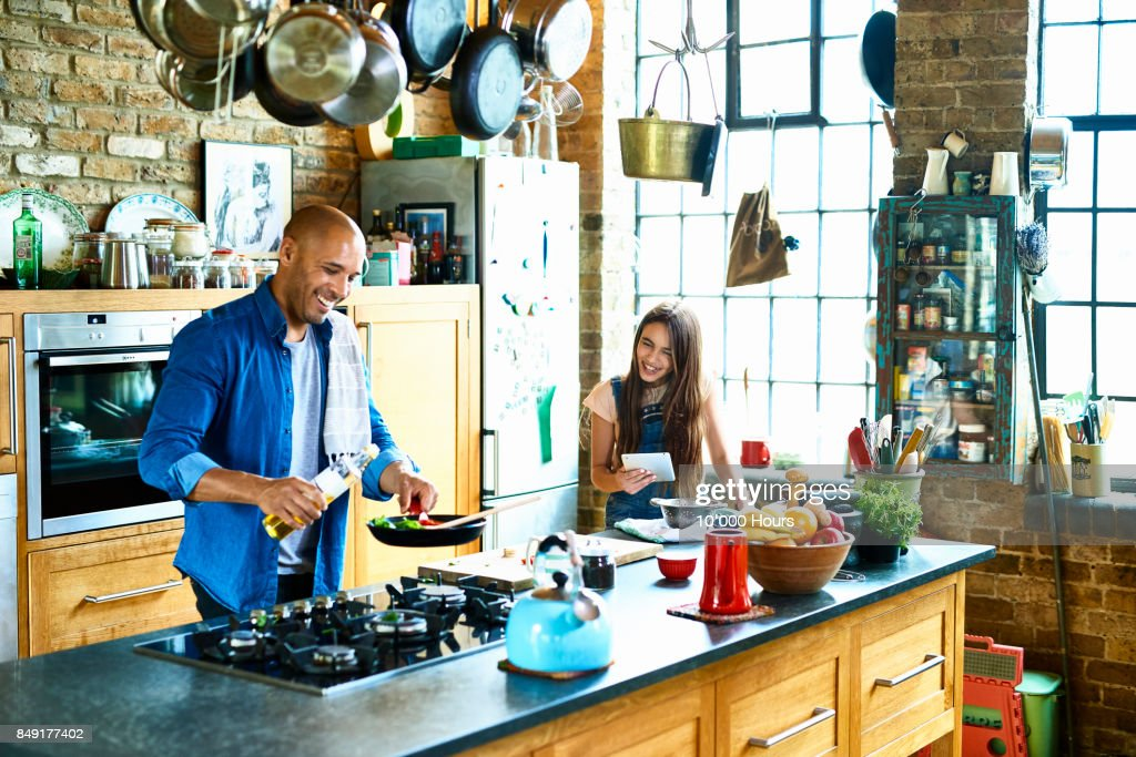 Father and daughter cooking together : Stock Photo