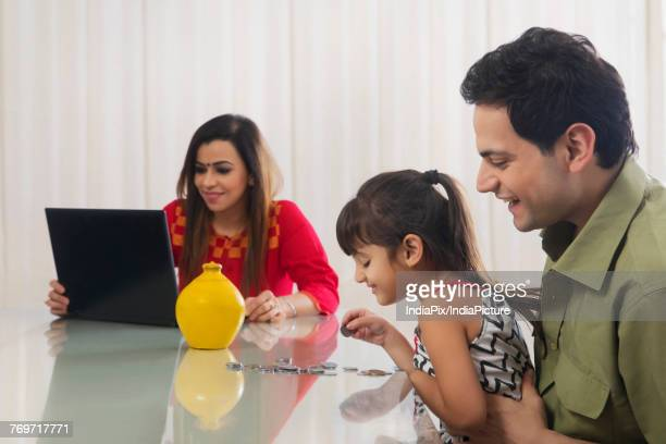 Father and daughter counting piggy bank coins and mother working on laptop