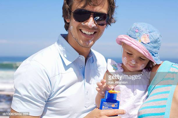 Father and daughter (12-18 months) covered in sunscreen on beach
