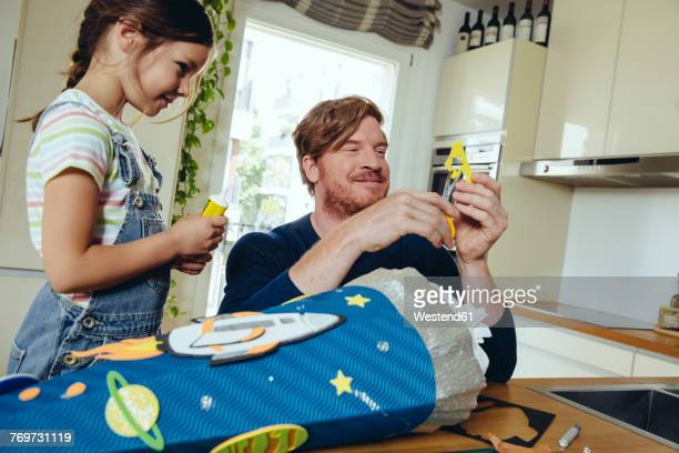 father and daughter creating her space themed school cone at home - der erste schultag stock-fotos und bilder