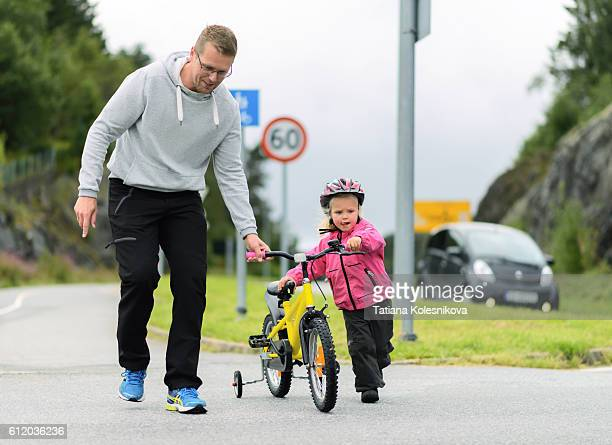 Father and daughter crossing a road with a bike