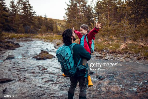 father and daughter crossing a stream - family with one child stock pictures, royalty-free photos & images