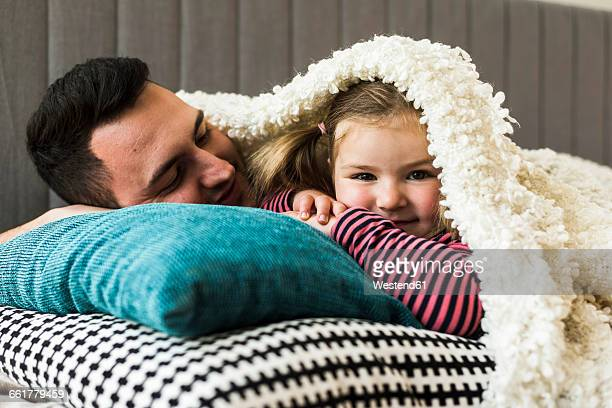 Father and daughter cuddling at home