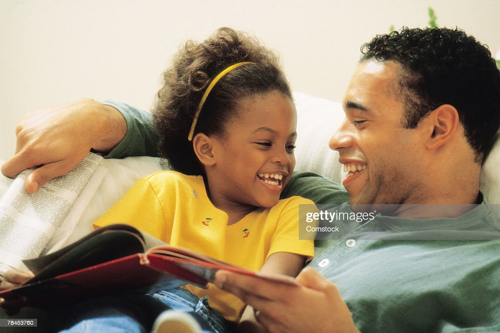 Father and daughter cuddling with book : Stockfoto