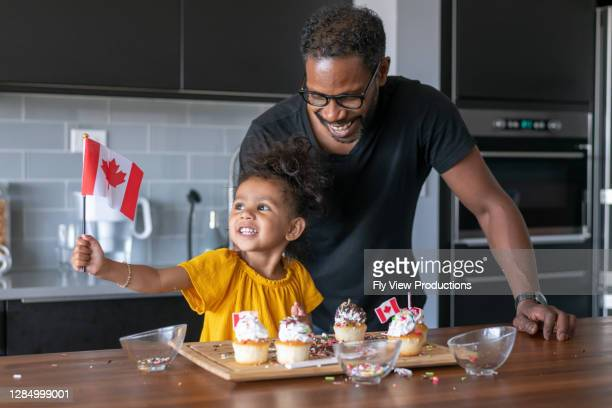 father and daughter decorate cupcakes while celebrating canada day at home - canada day stock pictures, royalty-free photos & images