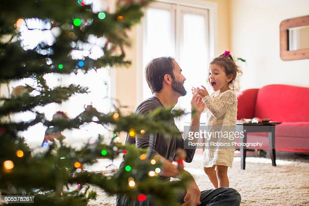 father and daughter decorating christmas tree - florida christmas stock pictures, royalty-free photos & images