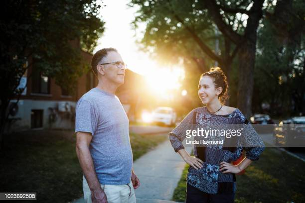 father and daughter discussing on a side walk at sunset - adult offspring stock pictures, royalty-free photos & images