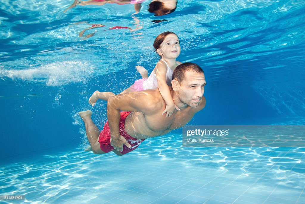 Father and daughter diving in the pool : Stock Photo