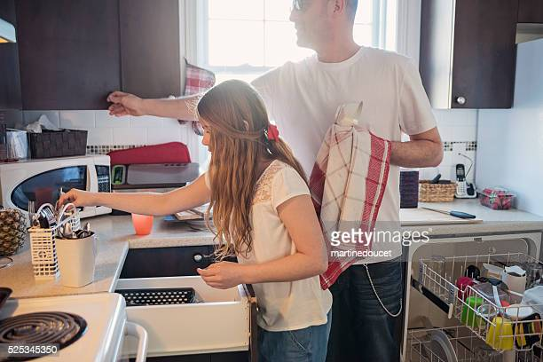Father and daughter doing domestic chores in kitchen.