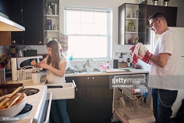 Father and daughter doing domestic chores in messy kitchen.