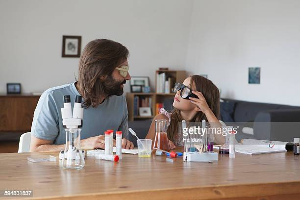 Father and daughter doing science experiment at table